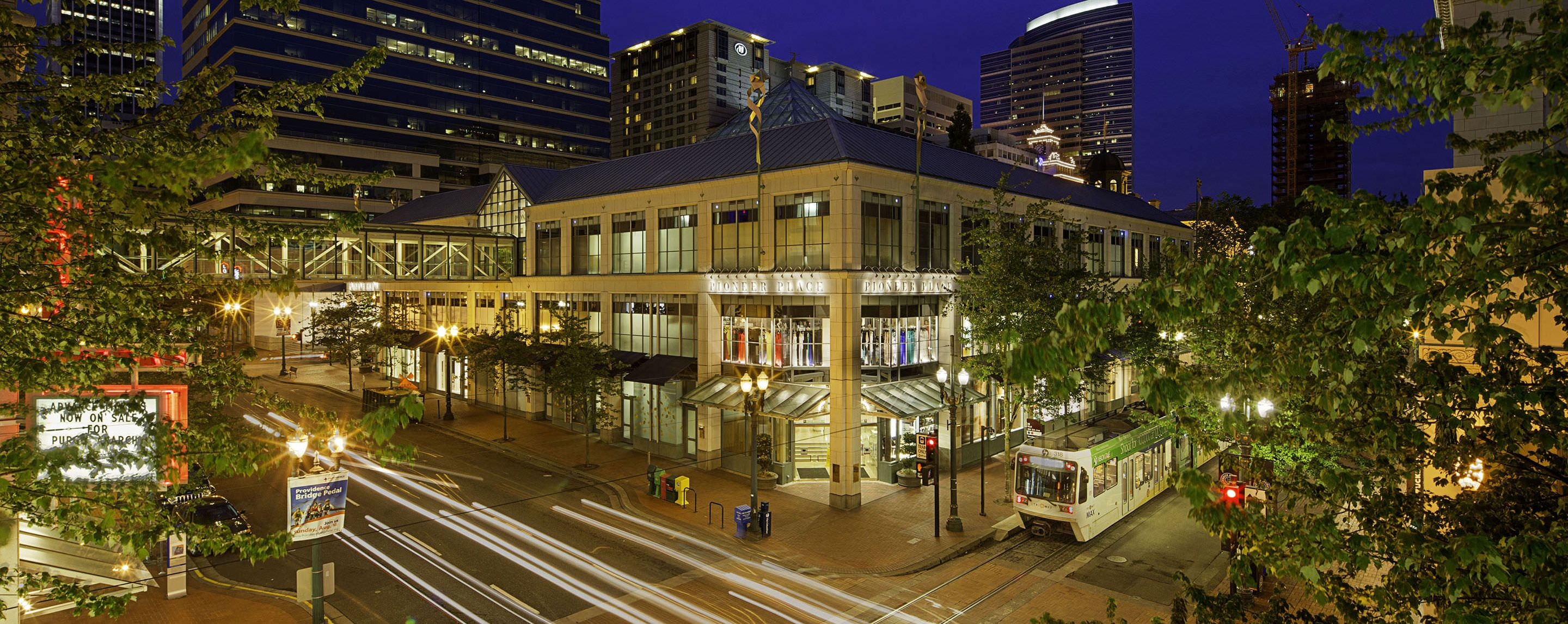 A GGP property illuminates the night with busy streets and public transportation outside.