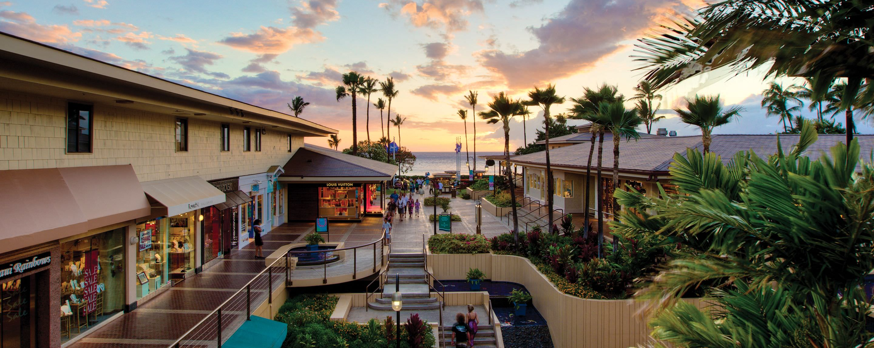 Guests can be seen strolling along the outside walkways and beautiful scenery of Whalers Village during dusk.