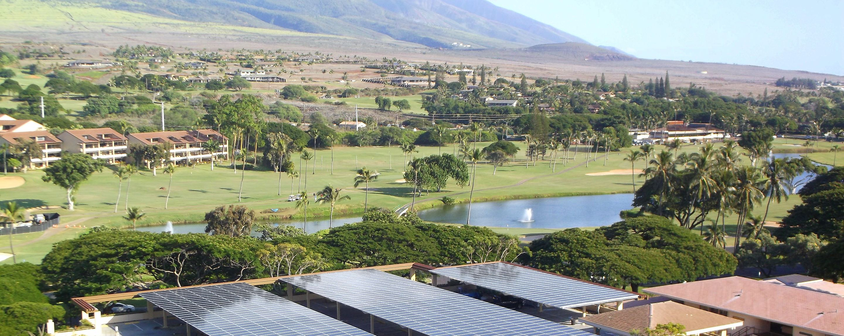 At dusk, a pond welcomes visitors outside of the Oakbrook Center entrance, which is lined with street lamps and trees