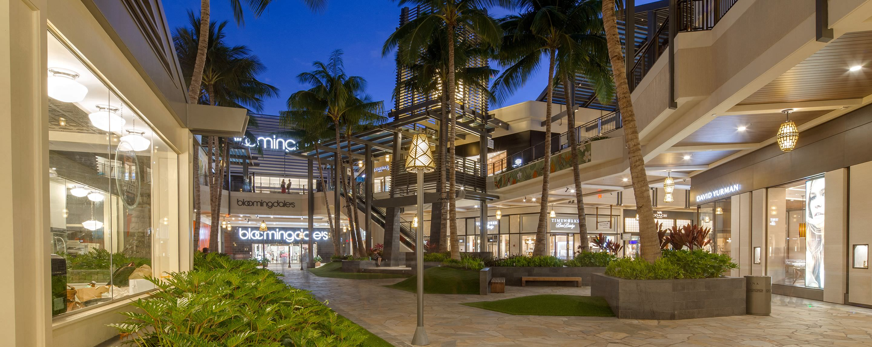 At dusk, an outdoor walkway of a GGP property is lined with lit up store fronts and palm trees.