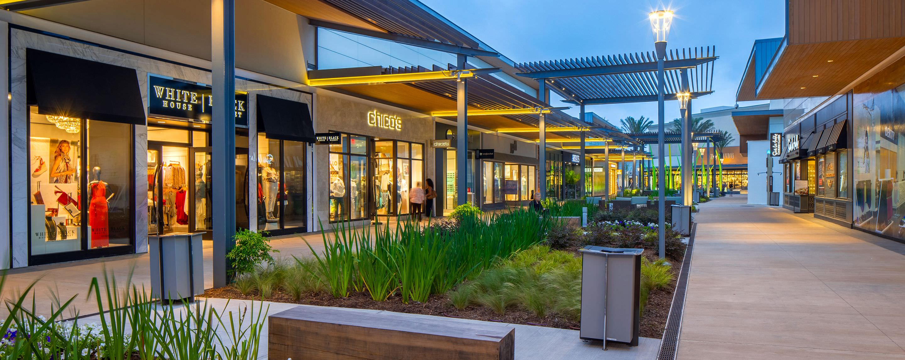 At night at a GGP property, an outdoor walkway is filled with store fronts welcoming shoppers.