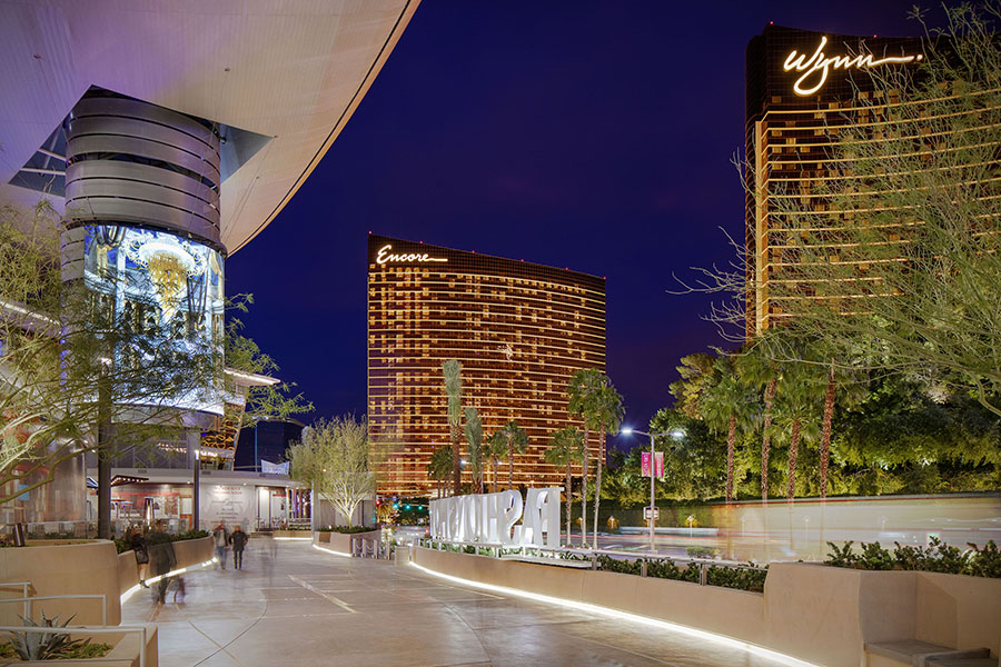 The open area leading into the Fashion show is lit up at night with several different trees and Las Vegas hotels in the background.