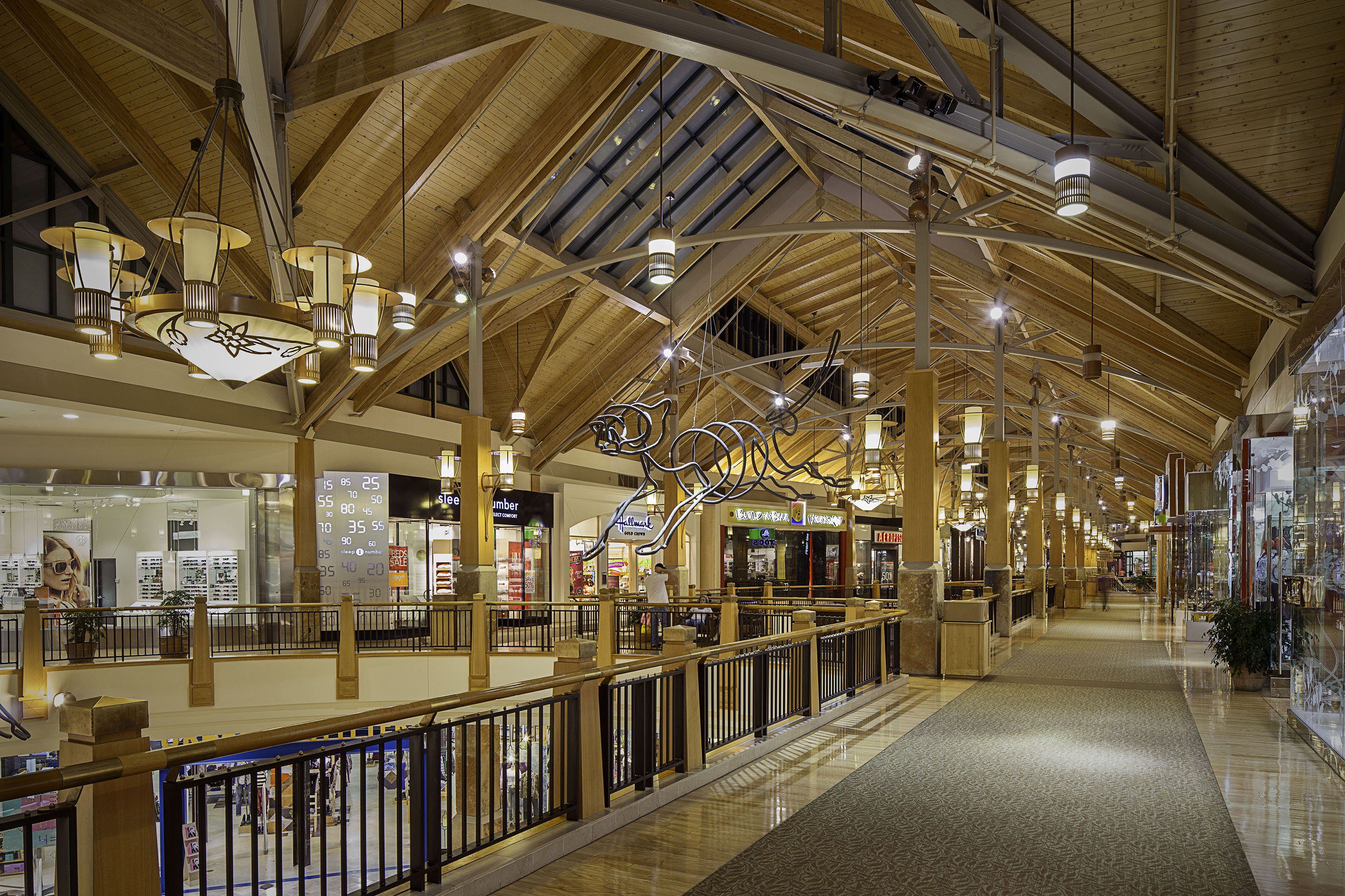 The interior of a Park Meadows walkway displays a variety of store fronts with lights and decor hanging from the ceiling.