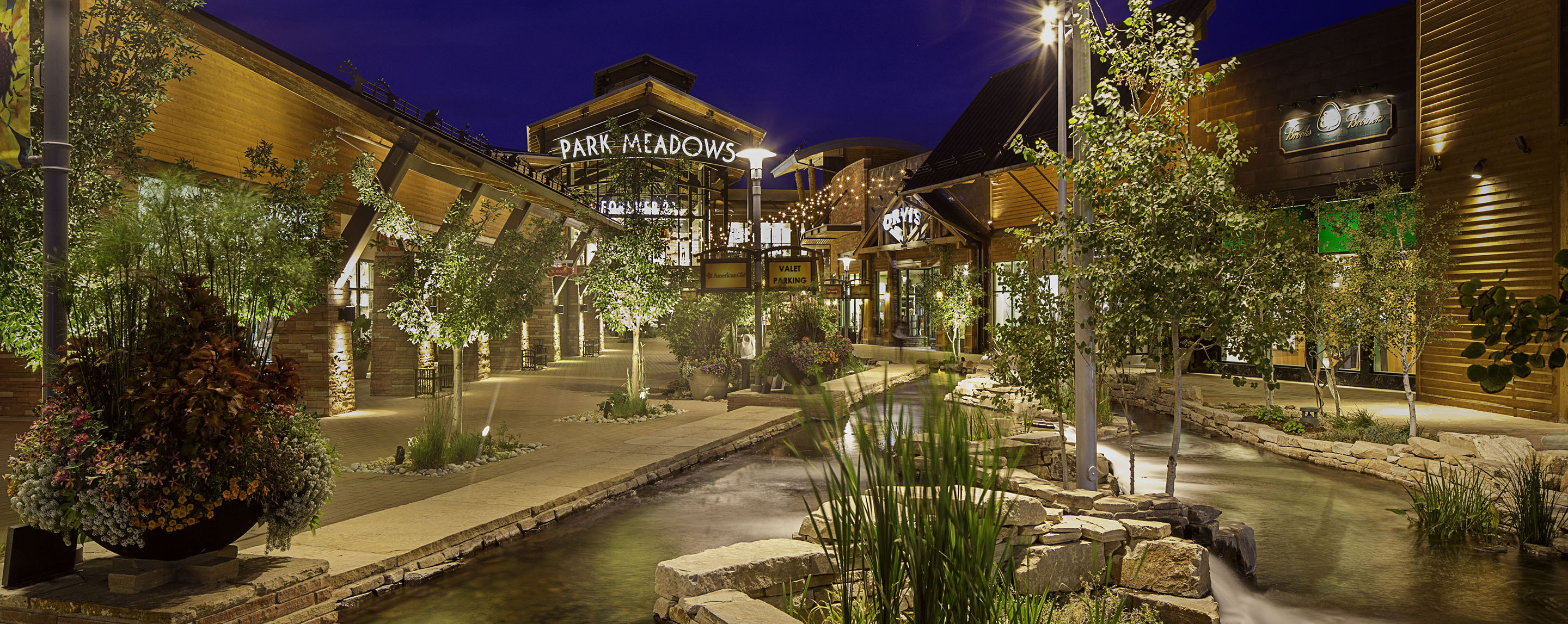 The walkway leading into Park Meadows is lit up at night with a decorative pond, trees, and lights welcoming visitors.