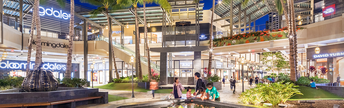 Visitors to the Ala Moana shopping center stroll through an outdoor atrium lined with palm trees at dusk.
